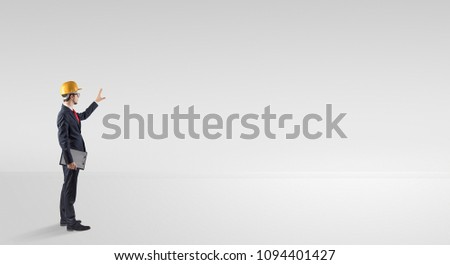 Young architect with construction helmet standing in an empty space and holding a plan #1094401427
