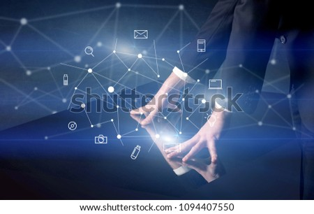 Male hands touching interactive table with blue mixed communication icons in the background #1094407550