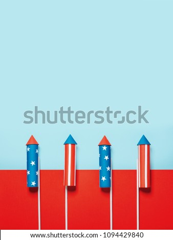 July 4, rockets for fireworks on a blue red background with space for text. in the style of minimalism #1094429840