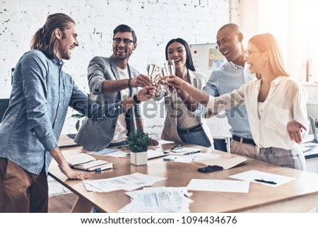 To our team! Group of young business people toasting each other and smiling while standing in the board room #1094434676