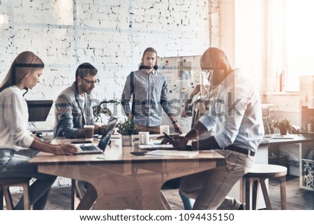 Sharing interesting ideas. Modern young man conducting a business presentation while standing behind the glass wall in the board room #1094435150