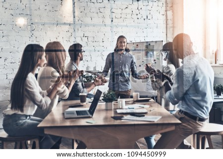 Incredible presentation. Modern young man conducting a business presentation while standing behind the glass wall in the board room #1094450999