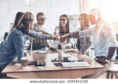 Great results. Group of business colleagues holding fists together in a symbol of unity while working behind the glass wall in the board room #1094451140
