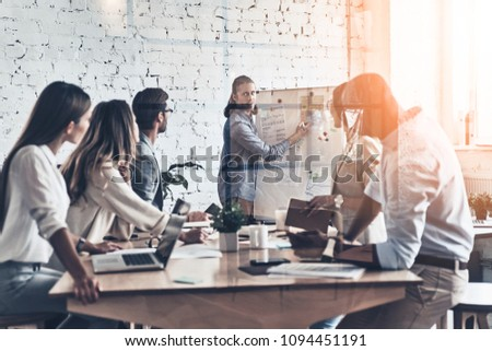 Putting ideas into something real. Modern young man conducting a business presentation while standing behind the glass wall in the board room #1094451191