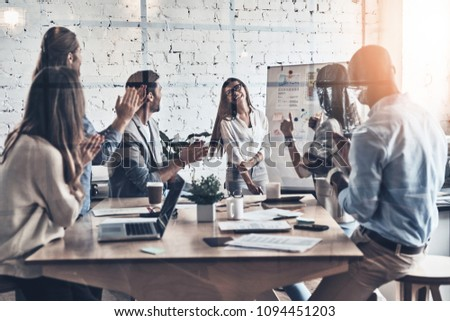 Real success. Modern young business people clapping and smiling while working behind the glass wall in the board room #1094451203