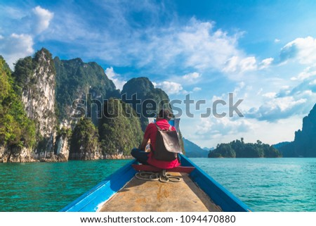 Man traveler relaxing on boat and joy view of limestone mountain, Cheow Lan lake, Ratchaprapha dam, Surat Thani, Travel adventur nature Thailand, Destination place Asia, Summer holiday vacation trip #1094470880