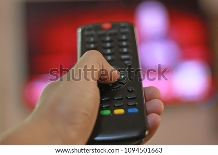 Remote control in hand closeup. watching TV and presses the button on the remote control. Remote control in hand closeup.  #1094501663