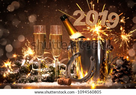 New Years Eve celebration background with pair of flutes and bottle of champagne in  bucket  and a horseshoe as lucky charm #1094560805