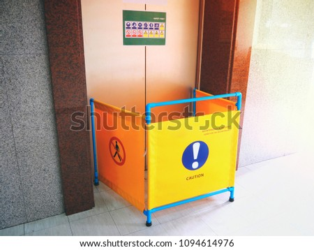 The safety first concept, Blocking space by technicians for repair and maintenance of elevator passenger. can see caution and don't pass sign , and label of many sign of safety on elevator door