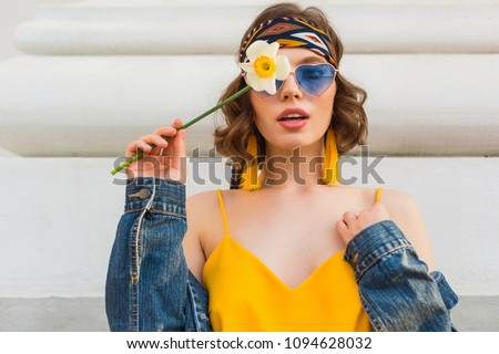 beautiful sexy woman in yellow stylish dress wearing denim jacket, holding flower, trendy outfit, hippie indie style, spring summer fashion trend, blue sunglasses, street fashion, trendy accessories #1094628032