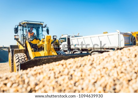 Construction workers doing earthworks with wheel loader and rubble truck #1094639930