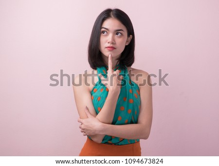 Cute asian woman in color casual dress thinking and imagination isolated on pink background