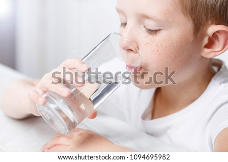 a little boy in the kitchen drinks clean water from a glass, clean water is a pledge of health #1094695982