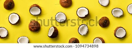 Pattern with ripe coconuts on yellow background. Top View. Copy Space. Pop art design, creative summer concept. Banner. Half of coconut in minimal flat lay style #1094734898