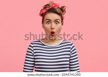 Omg, I can`t believe my eyes! Beautiful pinup girl in striped sailor turtleneck sweater, hears unbelievable news, says wow with amazement, stands against pink background. Emotive woman being excited #1094741390