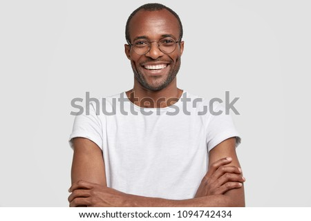 Portrait of unshaven pleased dark skinned male has warm broad smile, keeps hands crossed, rejoices hearing positive news, wears casual white t shirt and glasses. People and positive emotions #1094742434