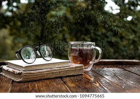 eyeglasses, Cup of tea and old books in garden. Rainy day, summer or autumn season. vintage style. soft selective focus.