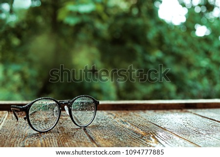 eyeglasses on wooden table, rainy day background. vintage style. copy space