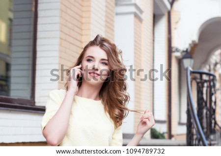 Young woman speaking on cellphone over city street background. #1094789732
