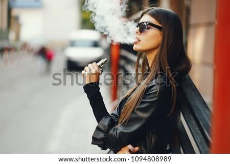 stylish girl smoking an e-cigarette as she is walking through the city #1094808989