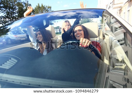 three girls driving in a convertible car and having fun #1094846279