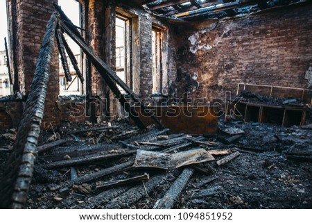 Ruins of burned brick house after fire disaster accident. Heaps of ash and arson, burnt furniture, collapsed roof, broken windows #1094851952