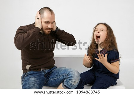 Picture of shocked young unshaven male in stylish clothes covering ears because of naughty spoiled female child who is crying and shouting loudly. People, family, relationships and problems concept