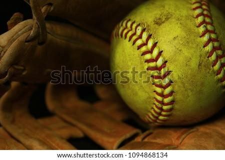 Yellow softball in a brown glove.