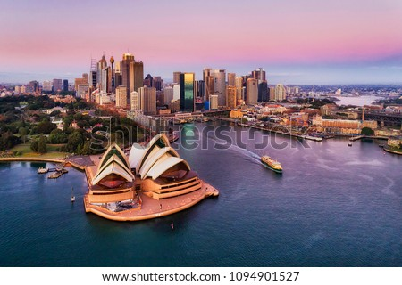 Pinkish colourful sunrise over Sydney city CBD on waterfront of Harbour around Circular quay with major architectural landmarks and symbols of Australia. #1094901527