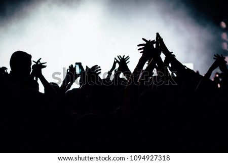 Silhouette of raised hands at the concert.  #1094927318