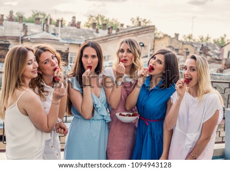 Girls Party. Beautiful Women Friends on the balcony Having Fun At Bachelorette Party. They eat strawberry #1094943128