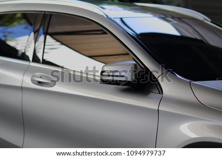 Rear-view mirror closed for safety at car park,  Side mirror of gray car , black tinted glass #1094979737