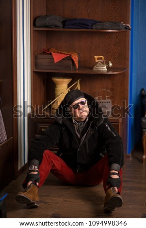 Handsome trendy senior man wearing stylish and expenive winter clothing sitting on wooden floor in tailor s shop with old or vintage accsessories. #1094998346