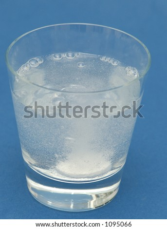 Headache tablet bubbling and dissolving in a glass of water #1095066