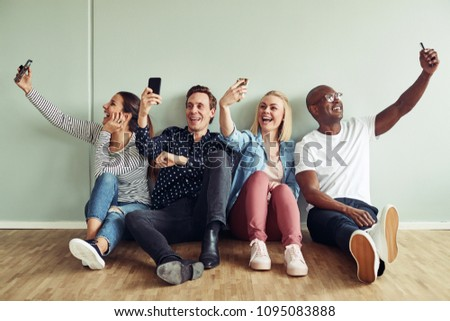 Group of diverse young businesspeople sitting on an office floor taking selfies together while on their break #1095083888