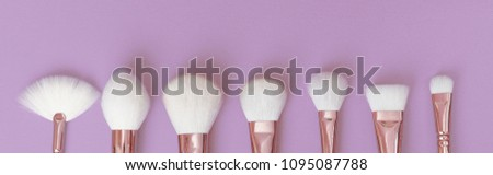 Professional luxury brushes for make-up made of gold metal on a violet background. #1095087788