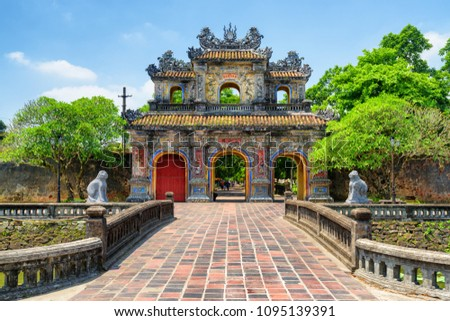 Scenic view of the East Gate (Hien Nhon Gate) to the Citadel with the Imperial City on summer sunny day in Hue, Vietnam. The colorful gate is a popular tourist attraction of Hue. #1095139391