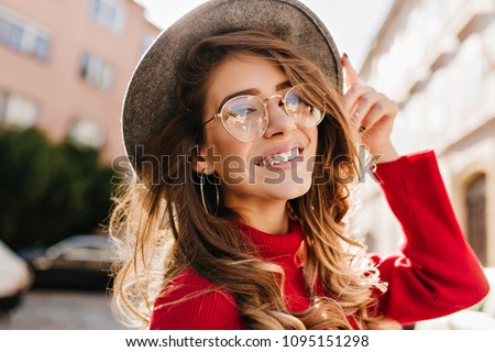 Close-up portrait of cheerful white woman in glasses touching her hat on blur background. Photo of fashionable girl with beautiful brown hair smiling to camera. #1095151298