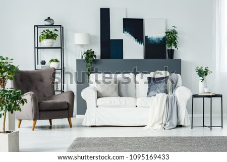 Front view of a white living room interior with a grey armchair, couch with pillows and art gallery #1095169433