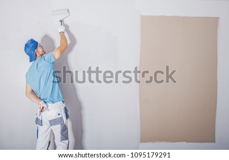 Room Painter at Work. Covering Darker Paint by Fresh and Lighter One. Apartment Renovation. Refreshing the Walls. Construction Theme. #1095179291