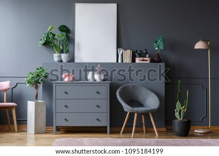 Grey armchair next to cabinet in flat interior with plants and mockup of white empty poster #1095184199