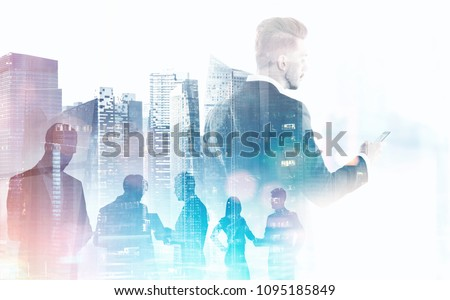 Businessman with a smartphone and business people silhouettes over a modern cityscape with skyscrapers. Business and communication in a modern company concept. Mock up toned image double exposure #1095185849