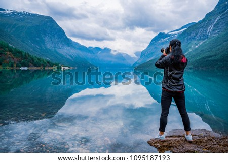 Nature photographer tourist with camera shoots Beautiful Nature Norway natural landscape. lovatnet lake. #1095187193