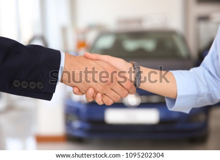 Young salesman shaking hands with client in car dealership #1095202304