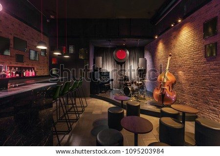 Modern jazz bar interior design, stage with black piano and cello, lamps above bar counter Royalty-Free Stock Photo #1095203984