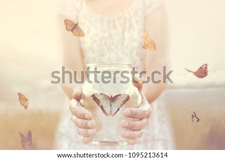 woman gives freedom to some butterflies enclosed in a glass vase Royalty-Free Stock Photo #1095213614