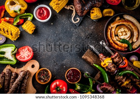 Assortment various barbecue food grill meat, bbq party fest - shish kebab, sausages, grilled meat fillet, fresh vegetables, sauces, spices, dark rusty concrete table, above copy space #1095348368