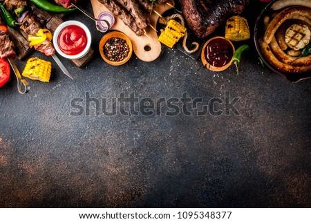 Assortment various barbecue food grill meat, bbq party fest - shish kebab, sausages, grilled meat fillet, fresh vegetables, sauces, spices, dark rusty concrete table, above copy space #1095348377