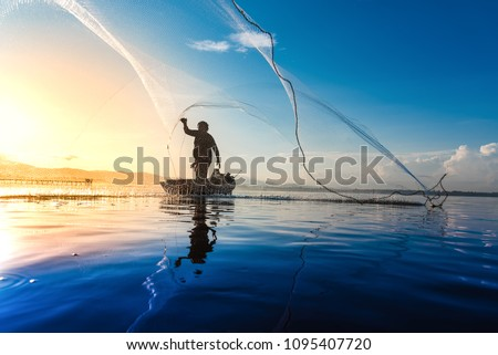 Silhouette of fishermen using coop-like trap catching fish in lake with beautiful scenery of nature morning sunrise. Beautiful scenery at Bang-Pra, Chonburi Province Thailand. Royalty-Free Stock Photo #1095407720