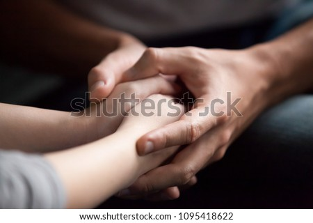 Male hands holding female, caring loving understanding man showing comfort and empathy, giving psychological support to woman in marriage relationships concept, couple reconciliation, close up view #1095418622